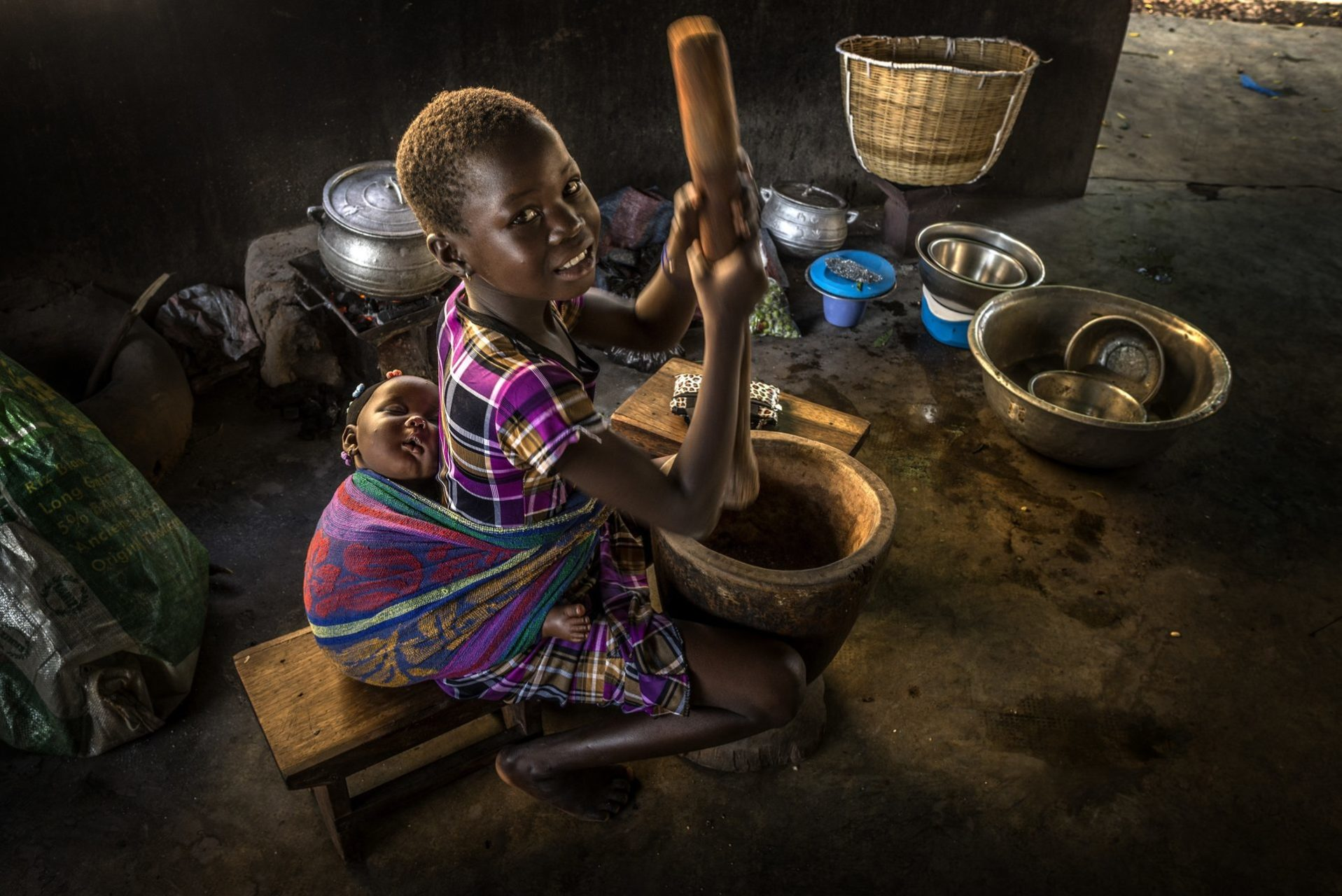 A young smiling west african girl, with a baby strapped to her back, prepares a meal in a large bowl with a wooden masher.