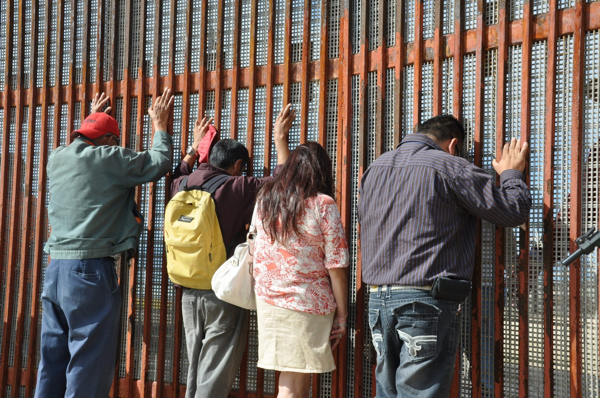 Three men and a woman facing large metal structure separating the U.S. and Mexico