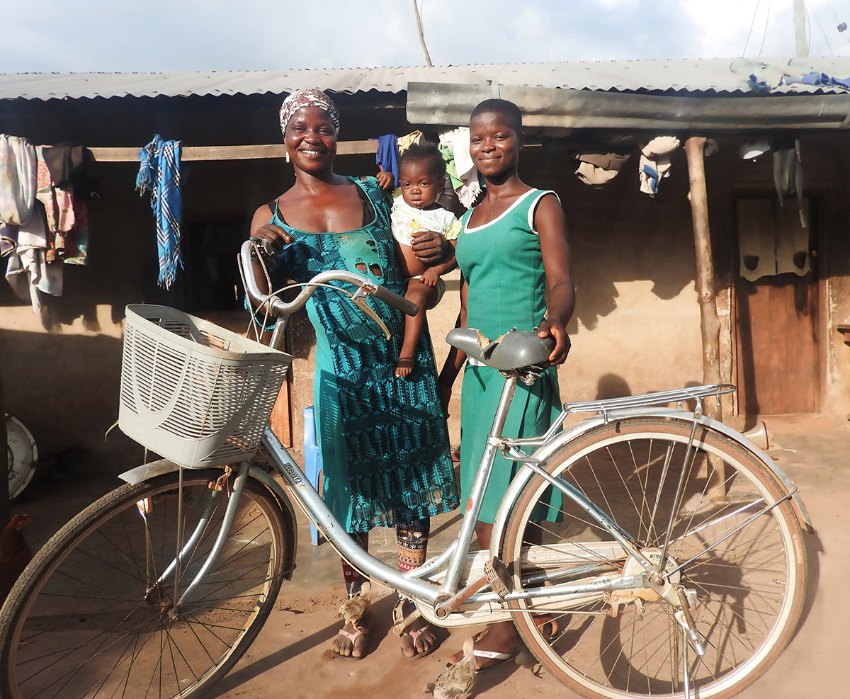 Two women stand in behind a bike, smiling as they pose for the camera. One woman holds a child in her hands.