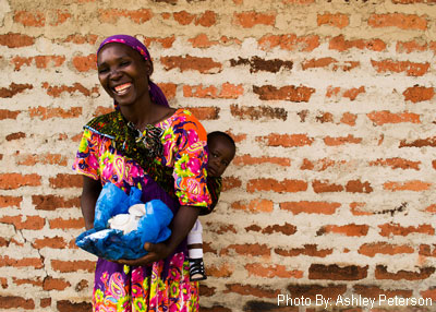 Women, smiling, carries mushrooms in a basket, and a small child on her back. She poses for the camera with a brick wall as the backdrop.