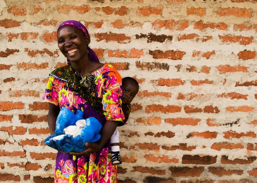 Woman smiles for the camera, as she holds a basket full of mushrooms in front of her, and a young child on her back. She stands in front of a brick wall.