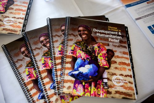 Photo of reports on a table. Report cover shows smiling women carrying mushrooms with a smile child on her back, posing in front of brick wall.