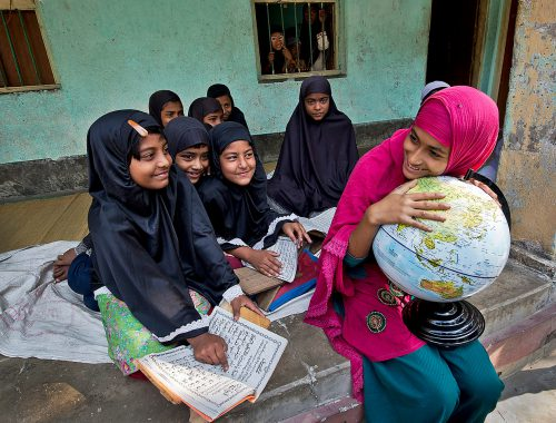 Young girls sit outside of classroom on the landing. The smile as they are learning. While all the girls are dressed in black, one girl stands out in pink, as she holds a globe.