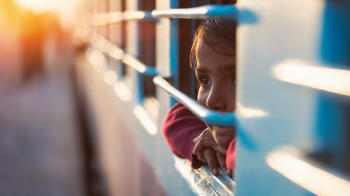 Small child peers out the window of a train during dusk.