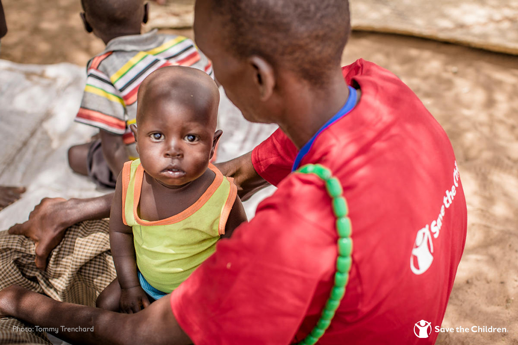 A young child sits in the lap of a humanitarian worker wearing a Save the Children t-shirt