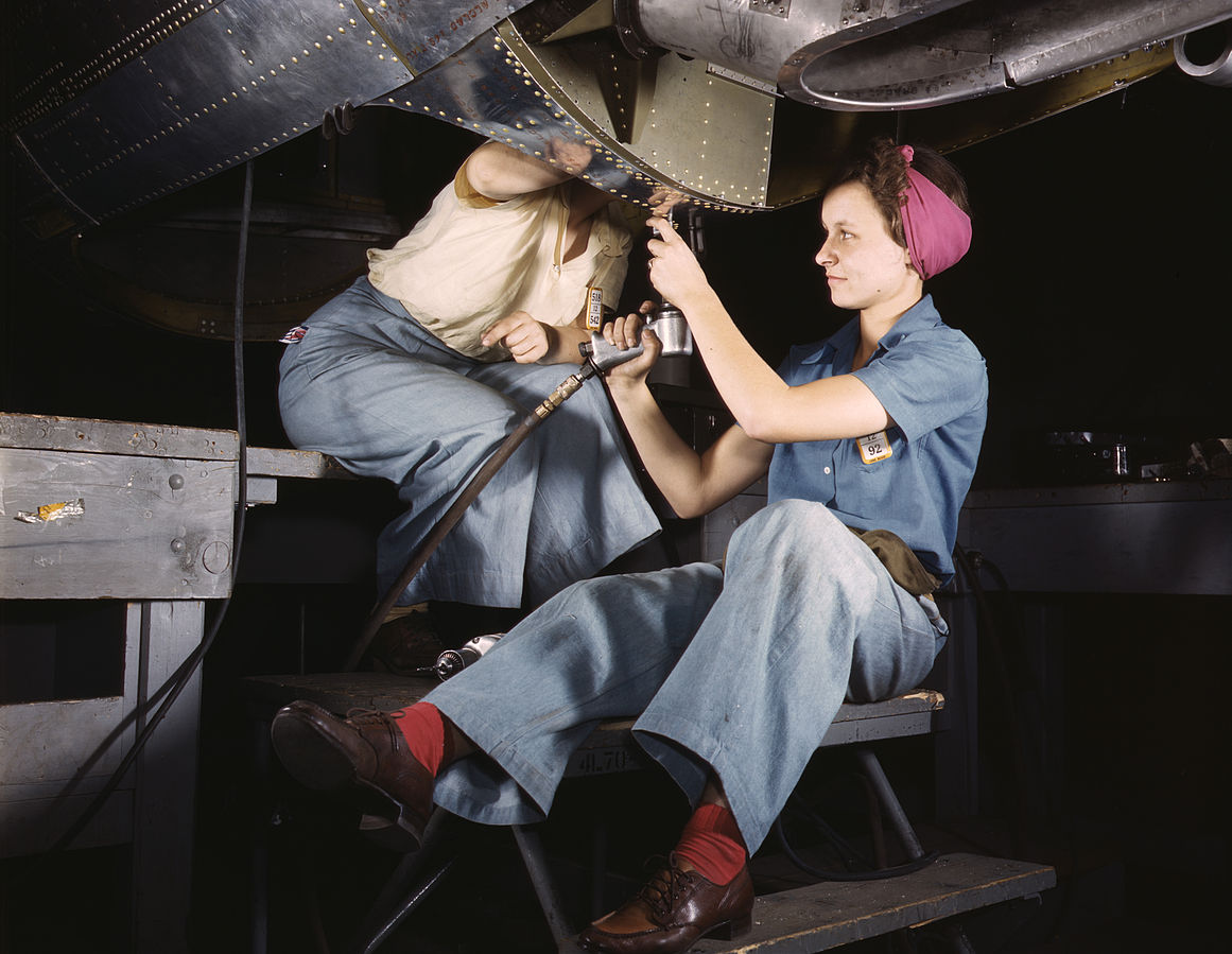 Two women workers work on a aircraft