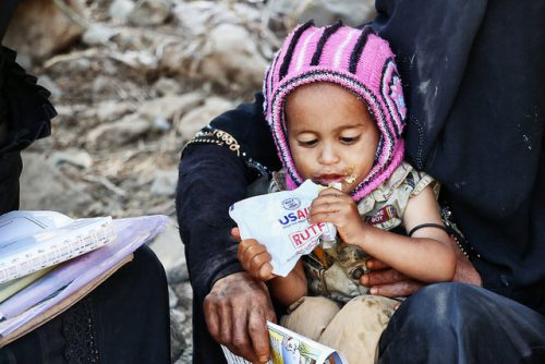 A small child eats a nutritional supplement meal provided by USAID in Yemen, while her mom holds her.