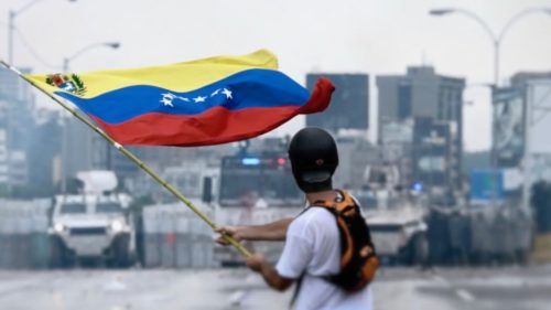 Young protester stands in the middle of a highway waving a Venezuelan flag