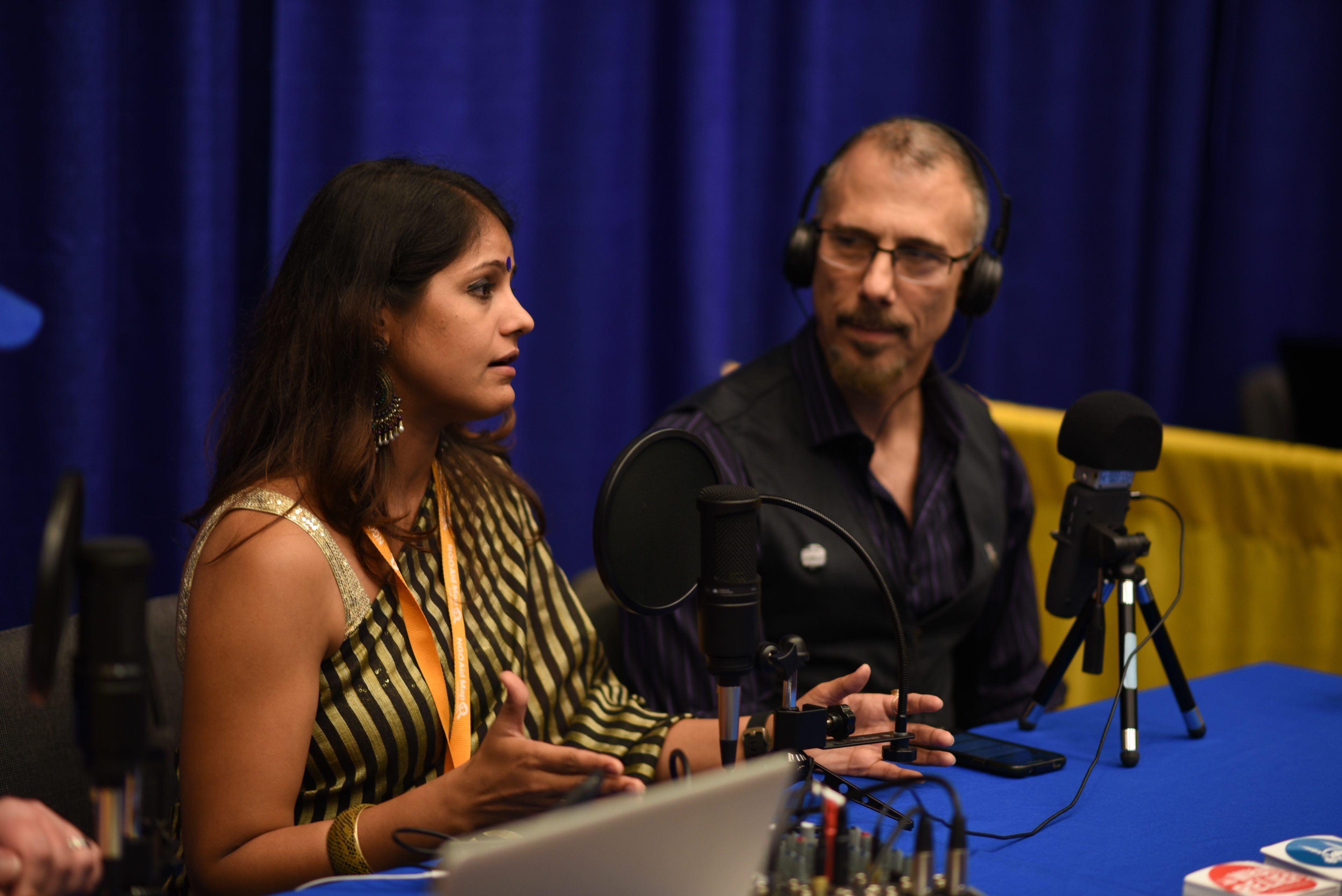 a woman and a man talk during a podcast recording