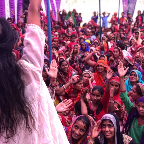 Women Stands in front of crowd, with her back to the camera, leading them as they raise their hand in agreement. The women are dressed in colorful garbs and smiling.