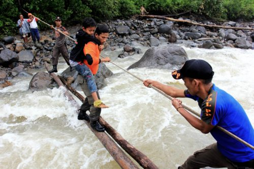 Using a rope, a man helps pull several men and boys cross a river on two thin logs.