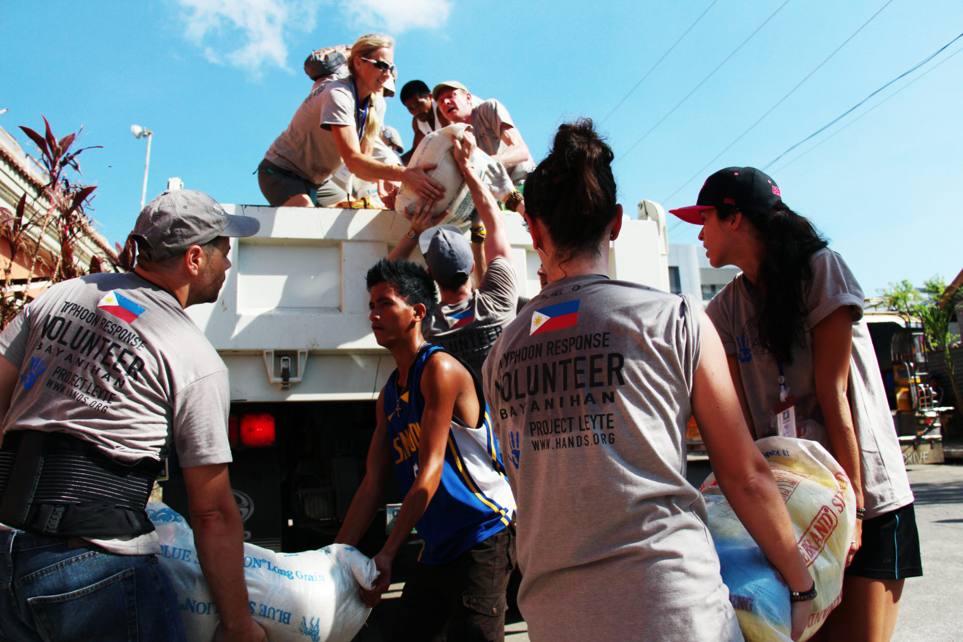 A group of workers load bags of food onto a truck