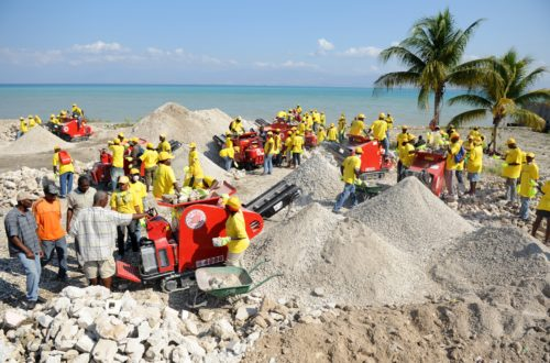 Workers crush rubble with machines on a beach in Haiti