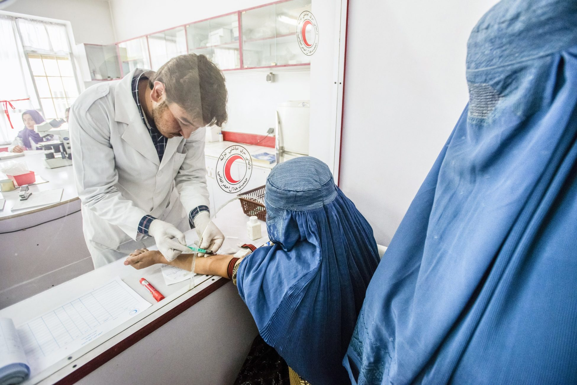 Laboratory staff Rohudin draws blood of woman wearing burka for blood test in laboratory of Central Hospital of Afghan Red Crescent Society, Kabul, Afghanistan