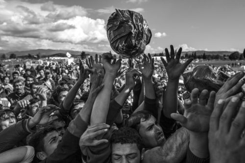 Hands reach for a package of food rations amid a large crowd of refugees