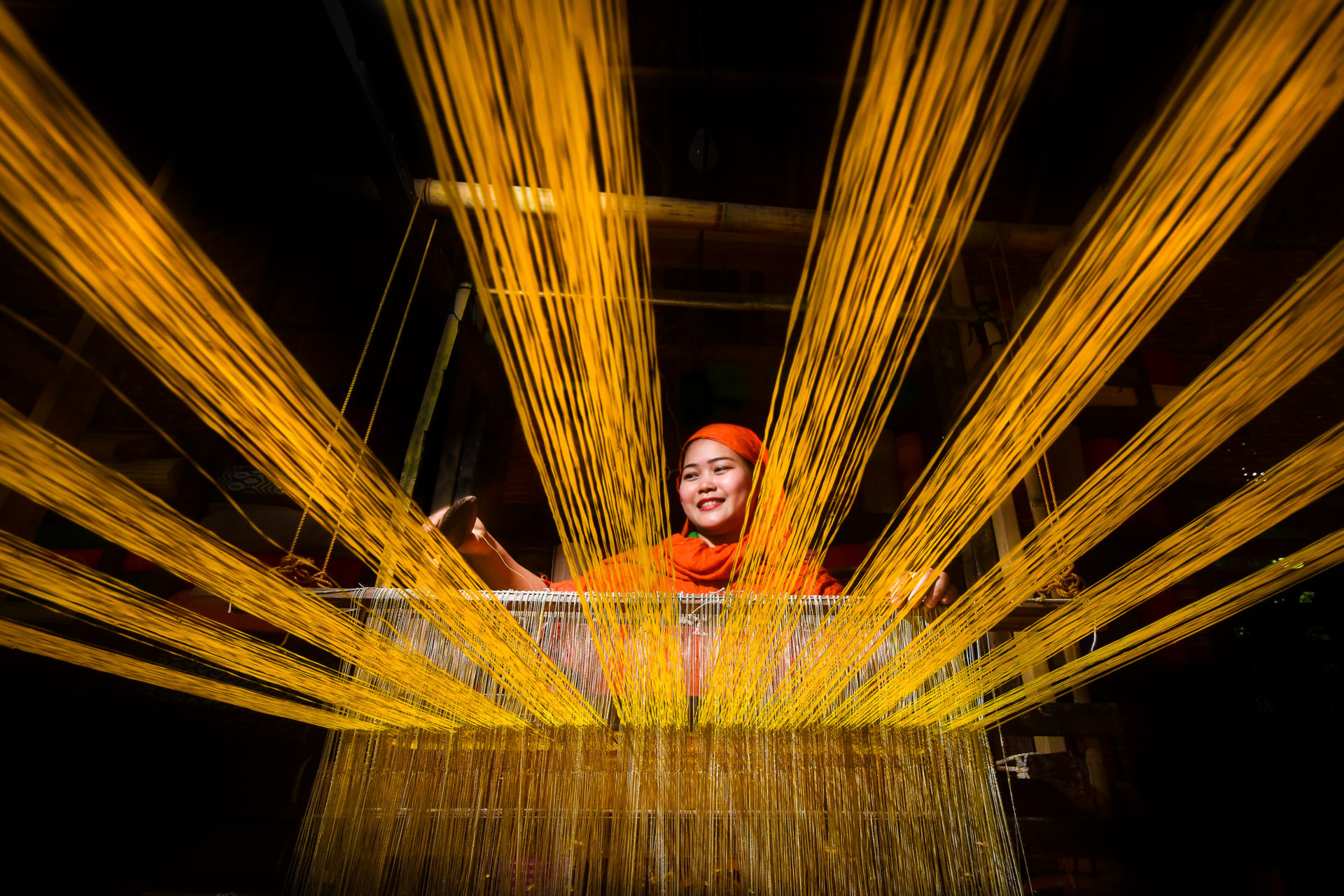 A women stands behind a loom weaving yellow thread