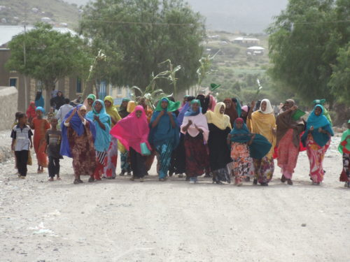 A group of women march happily down a dirt road