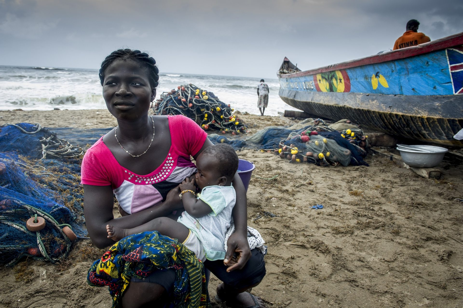 Women holds baby on the beach shore. Boat washed up ashore in the background.