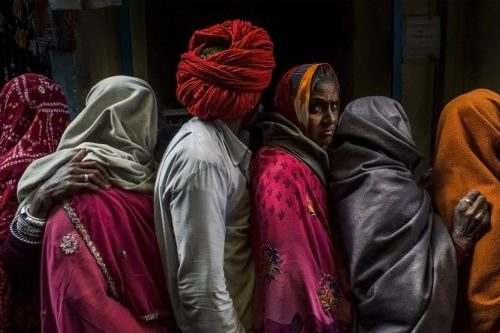 a group of men in women stand in line. All them are fully covered, faces hidden, with the exception of one woman who looks boldly at the camera.