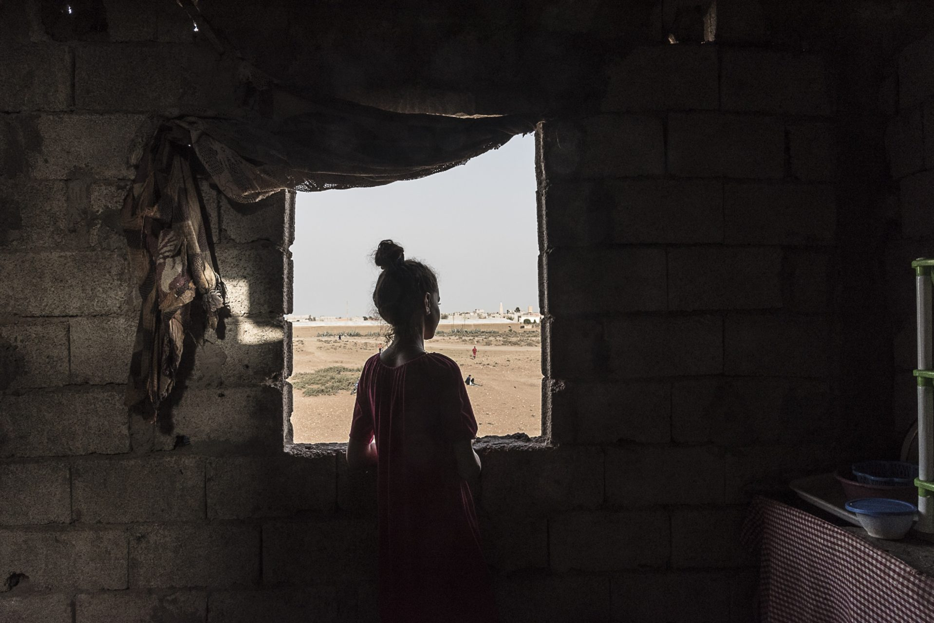 A young girl looks out the open window of a home