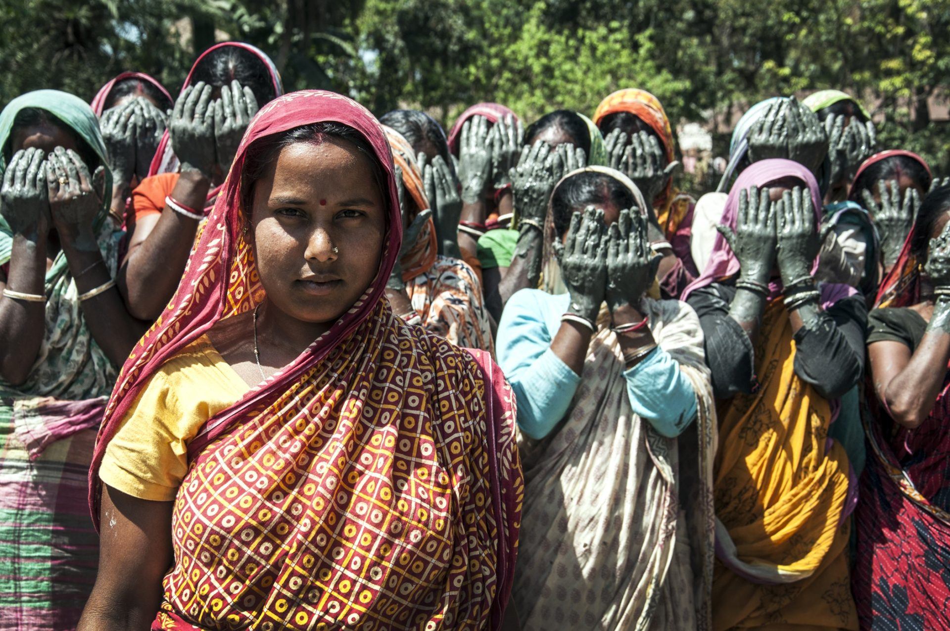 A woman stands at the forefront, staring directly into the camera. A group of women stand behind her cover their faces in protest.