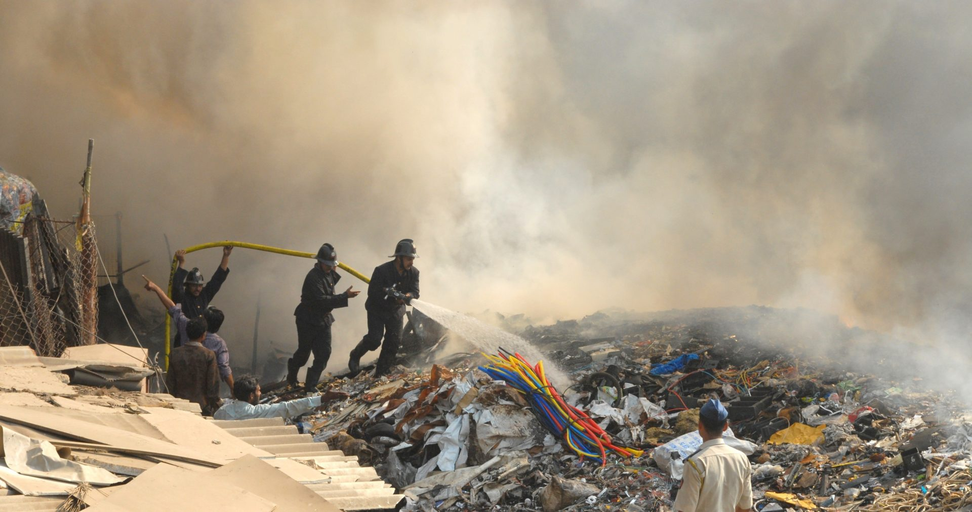 Firemen spray water on a large pile of smoldering rubble. Smoke fills the sky behind them.