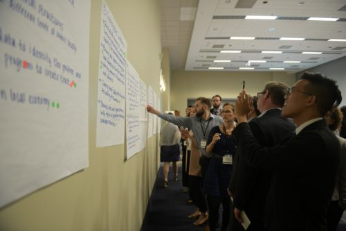 A group of men and women look at posters attached to a wall, discussing feedback.