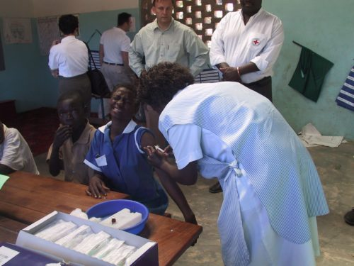 Women delivers measels vaccine to young girl in a clinic. A young boy sits at the table next to here waiting his turn. In the background, two gentlman watch as the shot is administered.