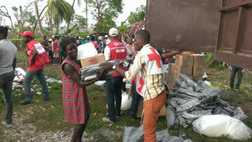 Red Cross aid worker hands over a number of items to a young woman. In the background, other items are distributed to a waiting crowd.