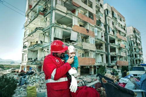 A rescue worker hold a small injured child in front of a partially destroyed apartment building
