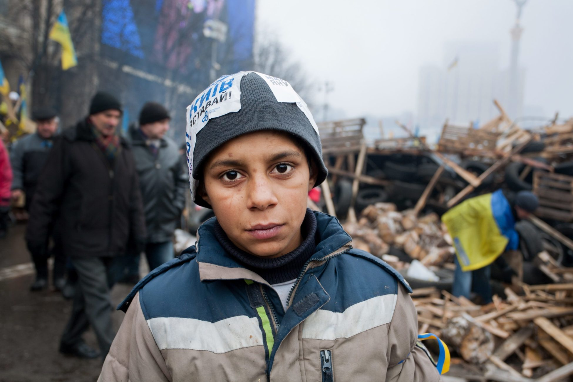 In the midst of a rubble, a young and determined looking boy, wearing a coat and warm hat, poses for the camera