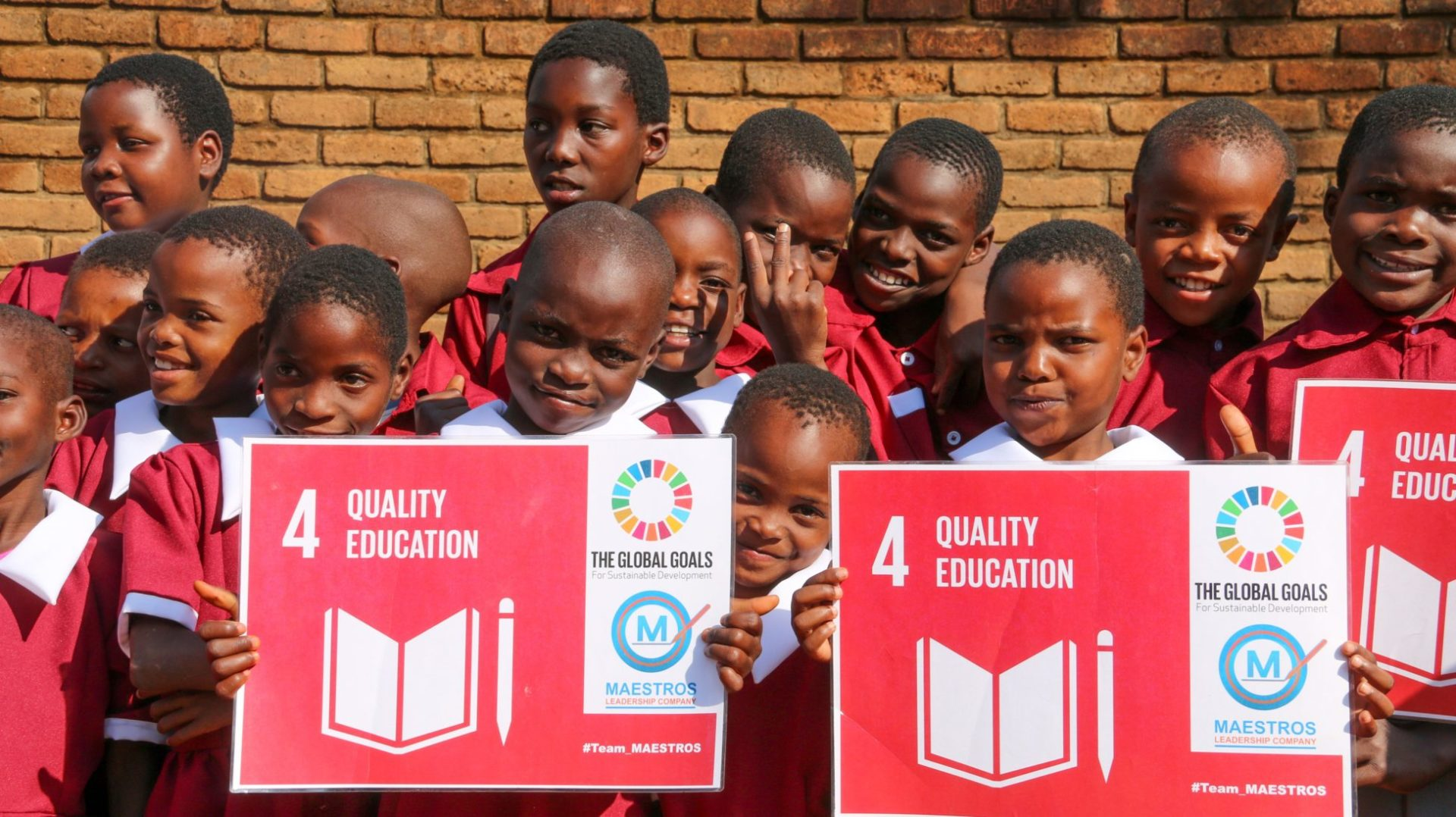 A group of school - children dressed in red school uniforms - pose for the camera, holding up placards with sustainable development goal number 4.