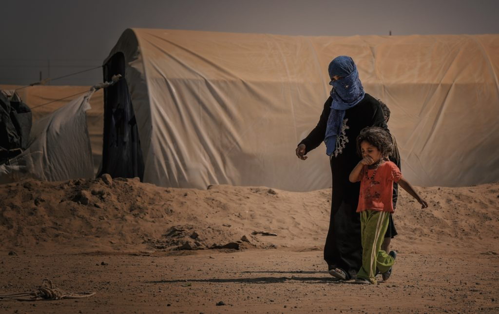 A woman and her young child walk in the middle of the desert passing by a large makeshift shelter for displaced people.