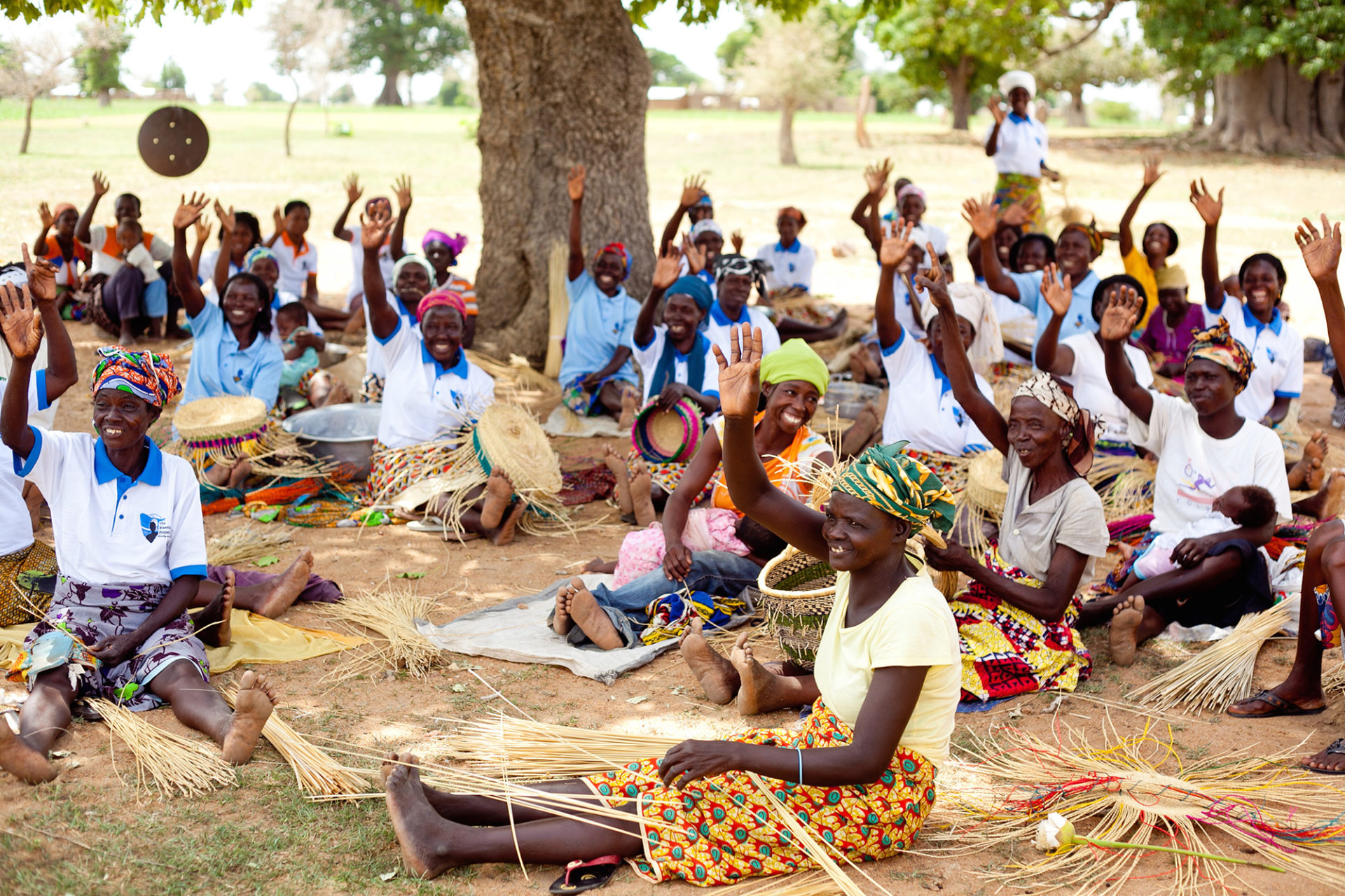 A group of women sit on the ground making baskets