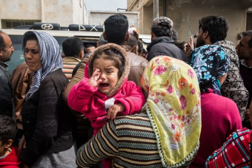 Woman holding her crying child in a crowd of people looking to find transport out of Afrin Syria