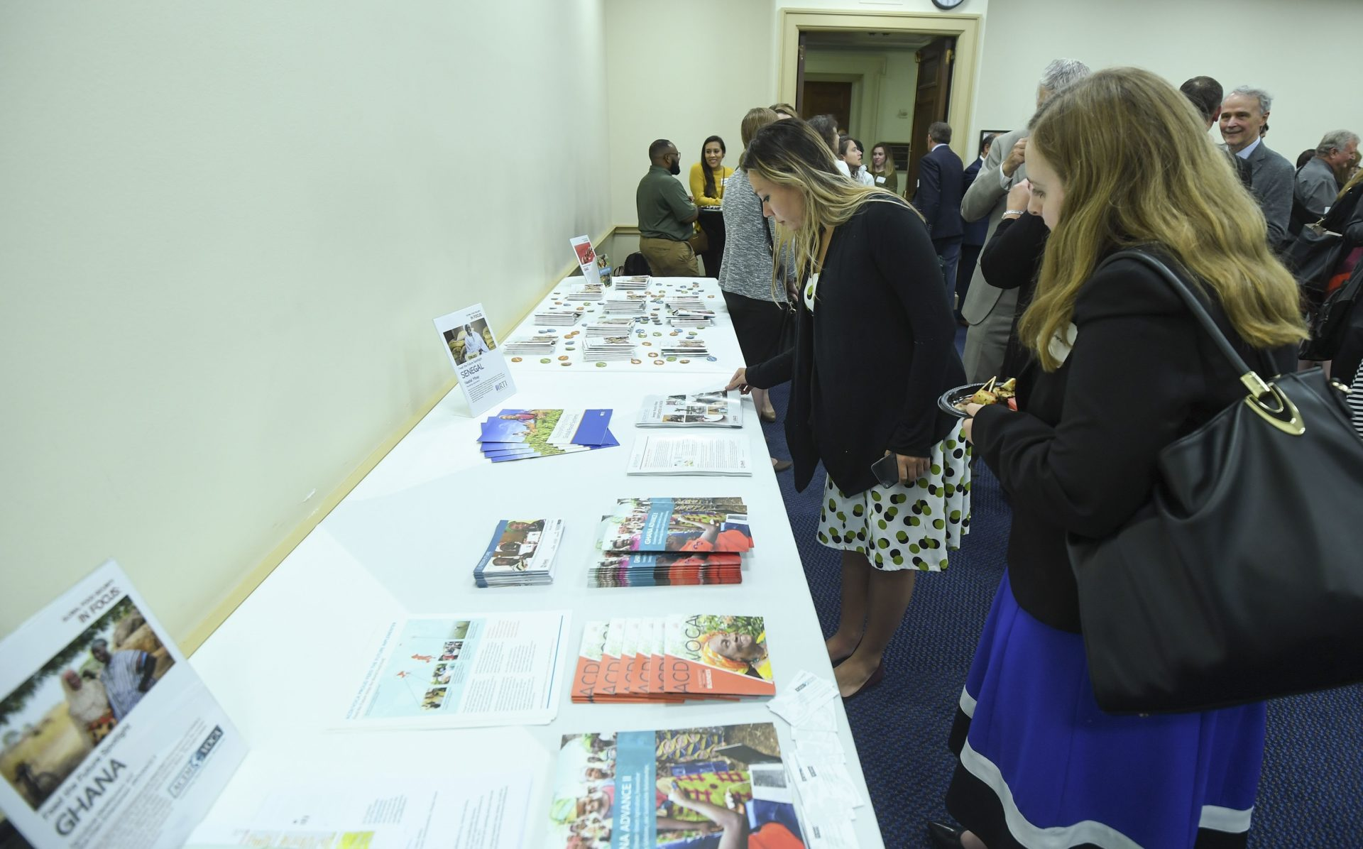 people gather around an information table that includes pamphlets and brochures