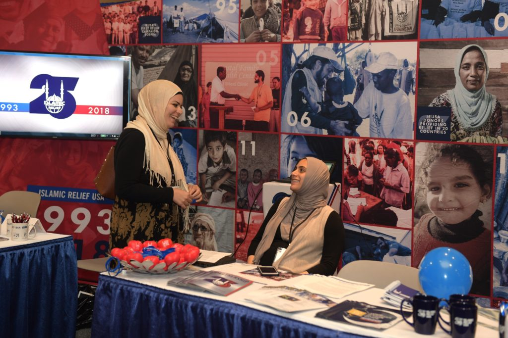 two women, one standing, on sitting, facing one another at the booth covered in color images from Islamic Relief.