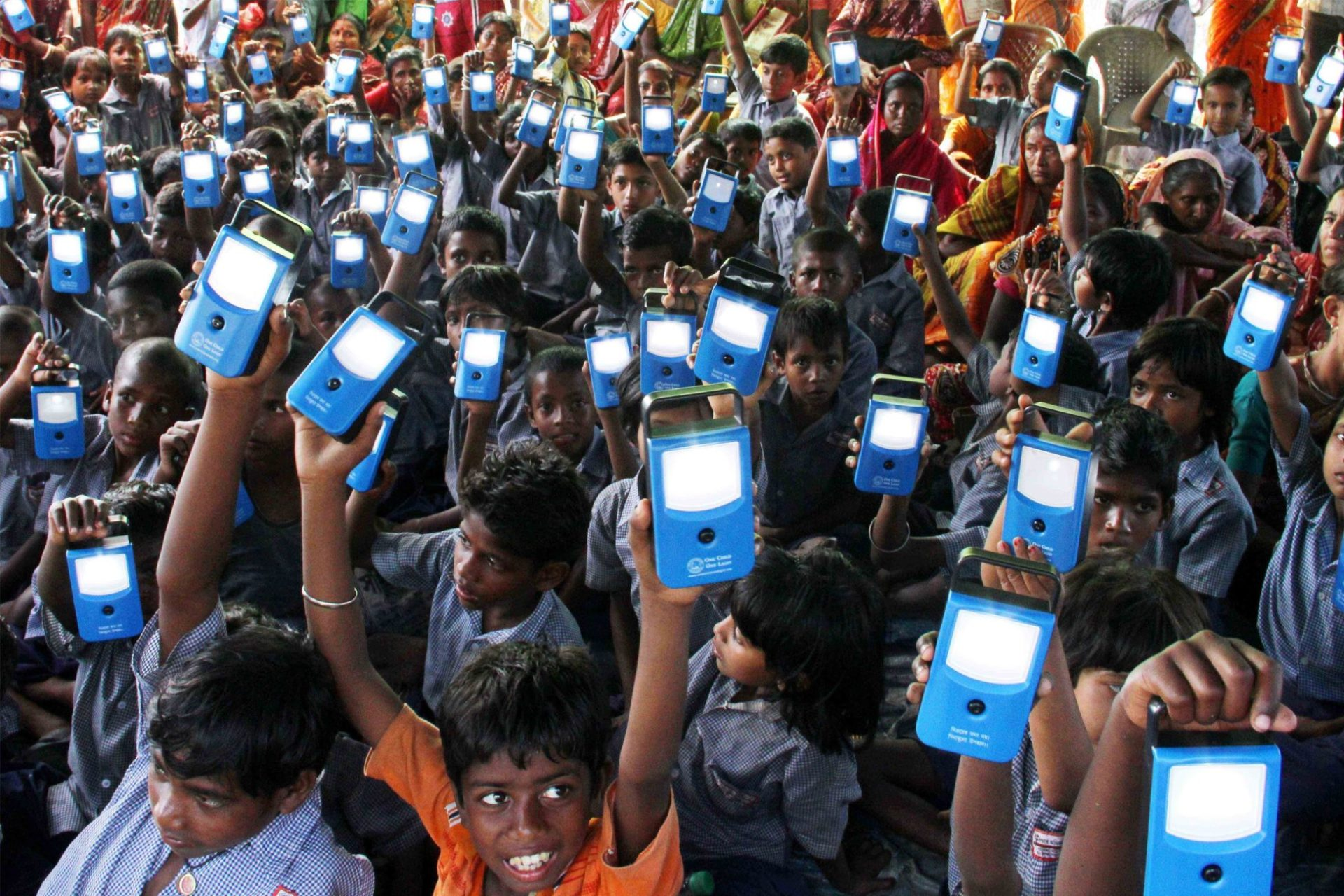 Young children raise their blue digital devices toward the sky.
