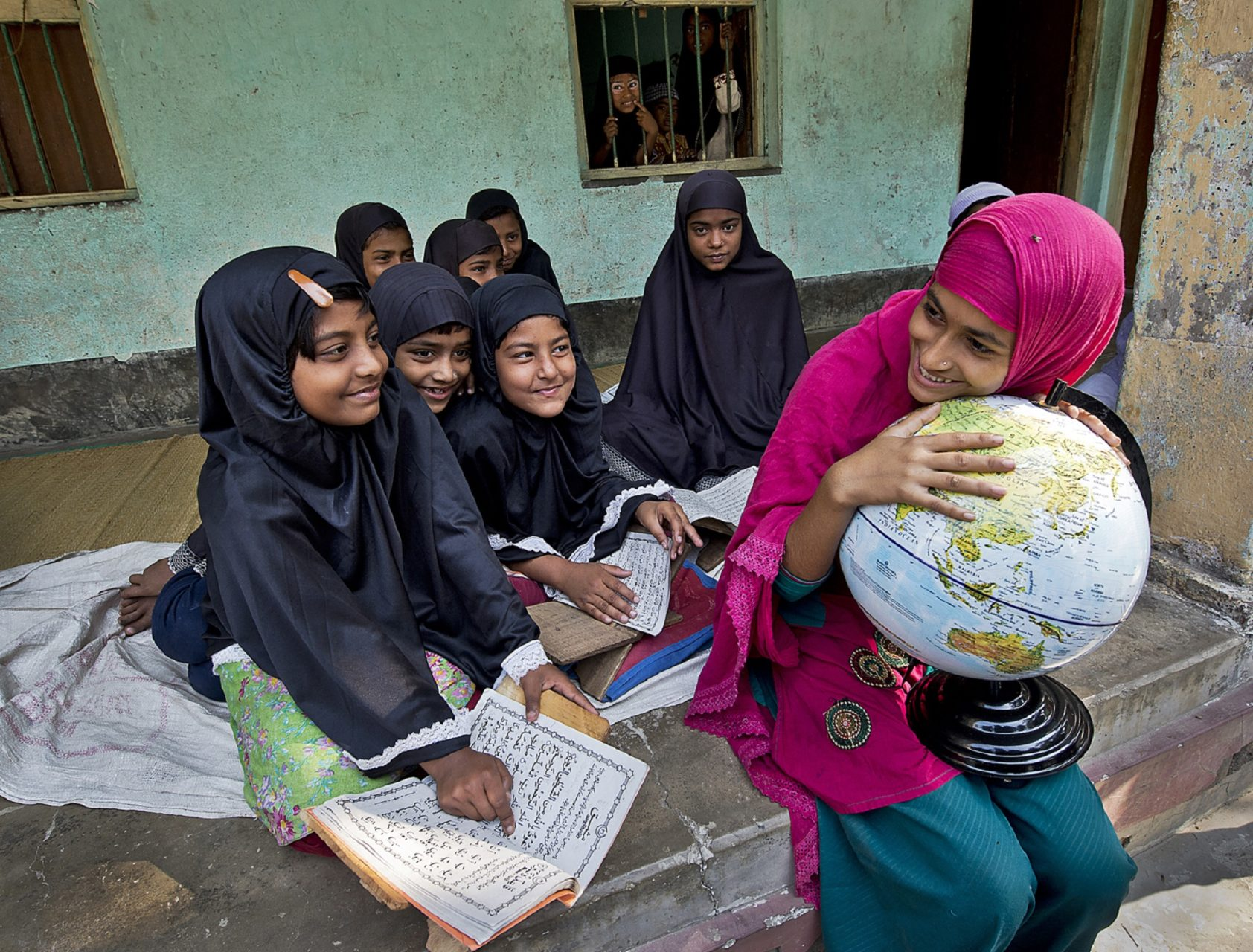 Girls reading and laughing. One girl holds to a globe