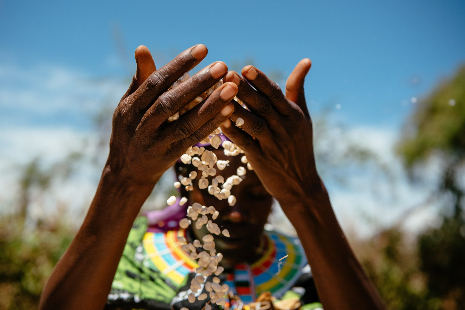 close up of woman letting corn spill through her hands.