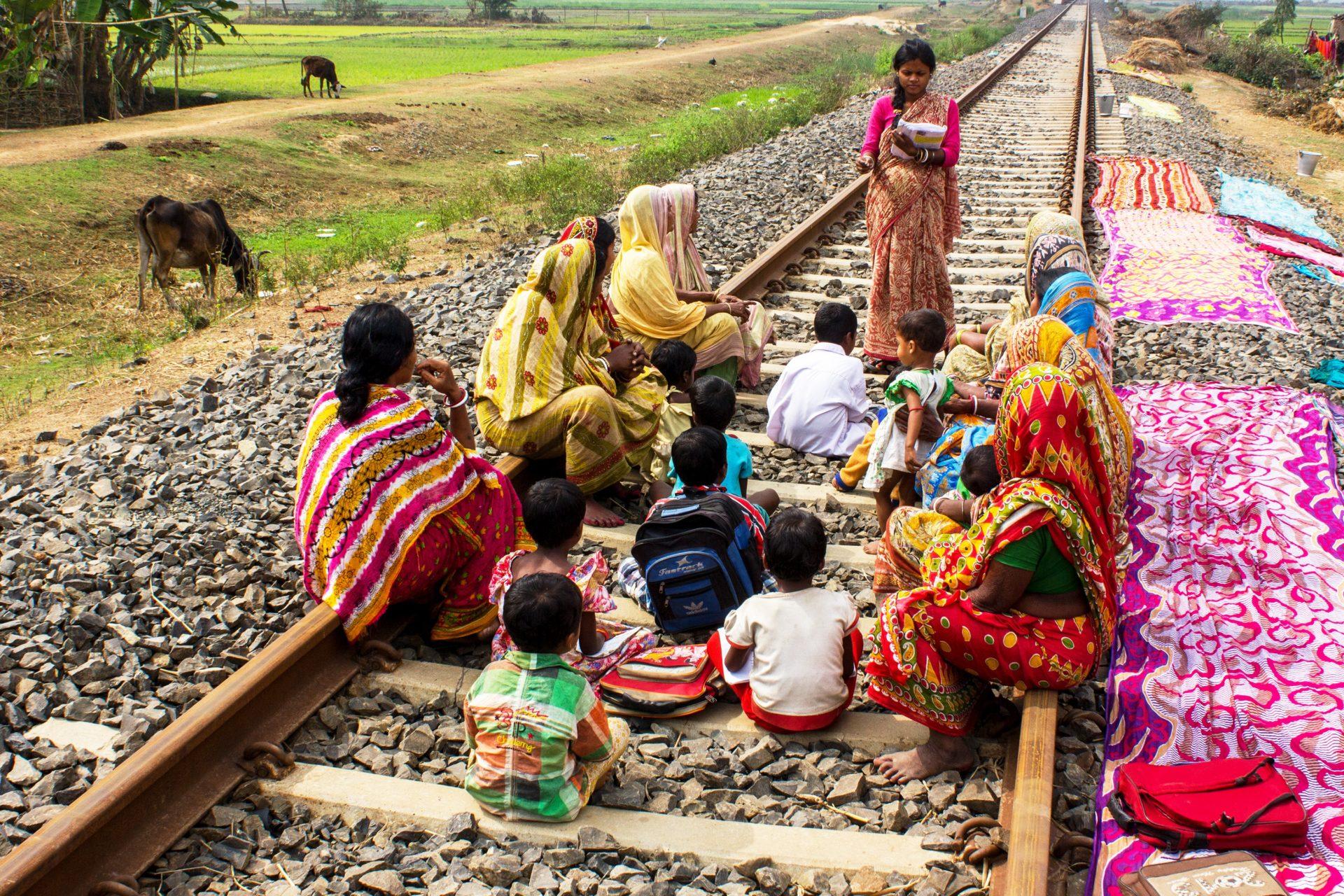 Women teaches women and children on a train track.