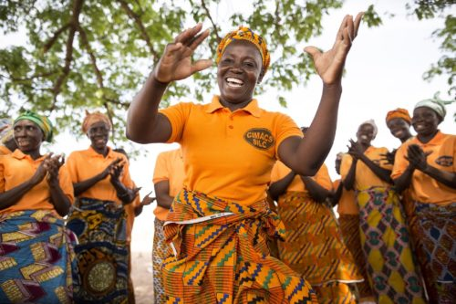 Members of CRS-supported SILC groups (Savings and Internal Lending Communities) dance together during a meeting in Awaradoni village, Upper East Region, Ghana. These women have begun making and selling shea nut butter, straw baskets, and parboiled rice ever since interrupted weather patterns related to climate change have inhibited their abilities to earn livelihoods through farming. Awaradoni village, Talensi District, Upper East Region, Ghana, West Africa. March 19, 2016 - Photo by Jake Lyell for CRS.