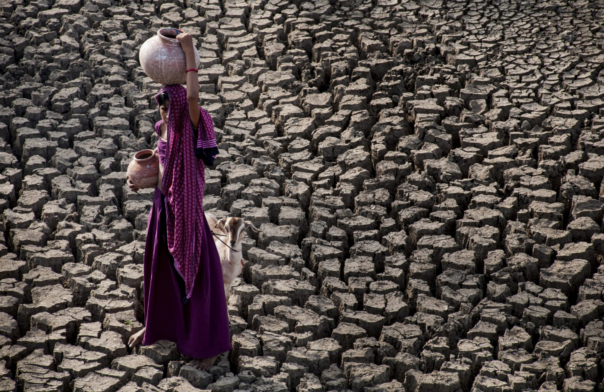 young girl carries water in her head and on her head in a water scarce environment