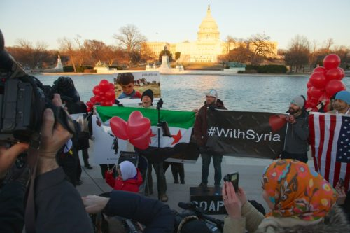 """people at the tidal basin holding signs that say """"with Syria"""""""