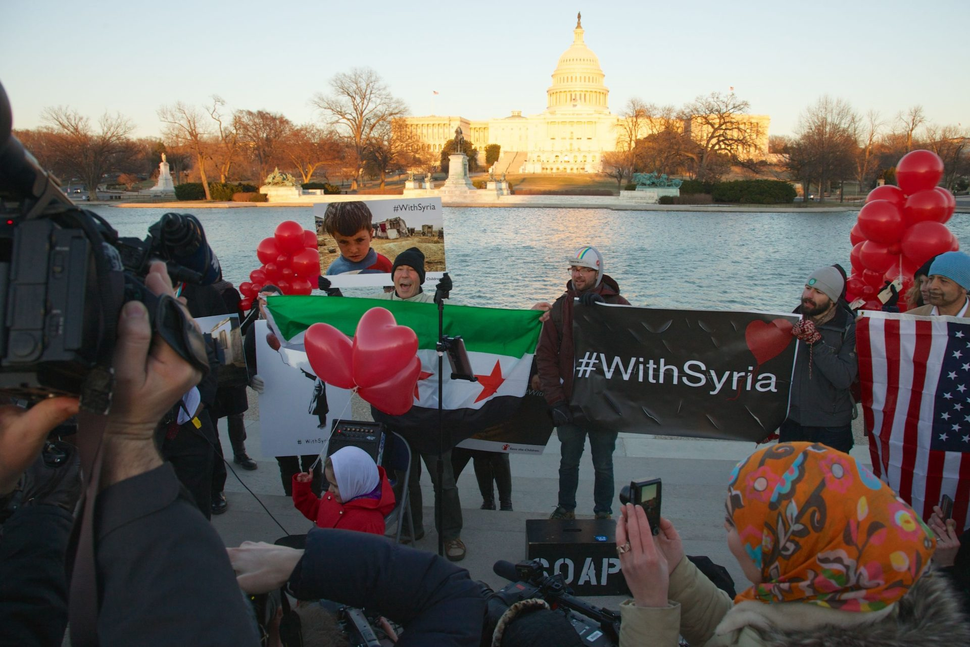 "people at the tidal basin holding signs that say ""with Syria"""