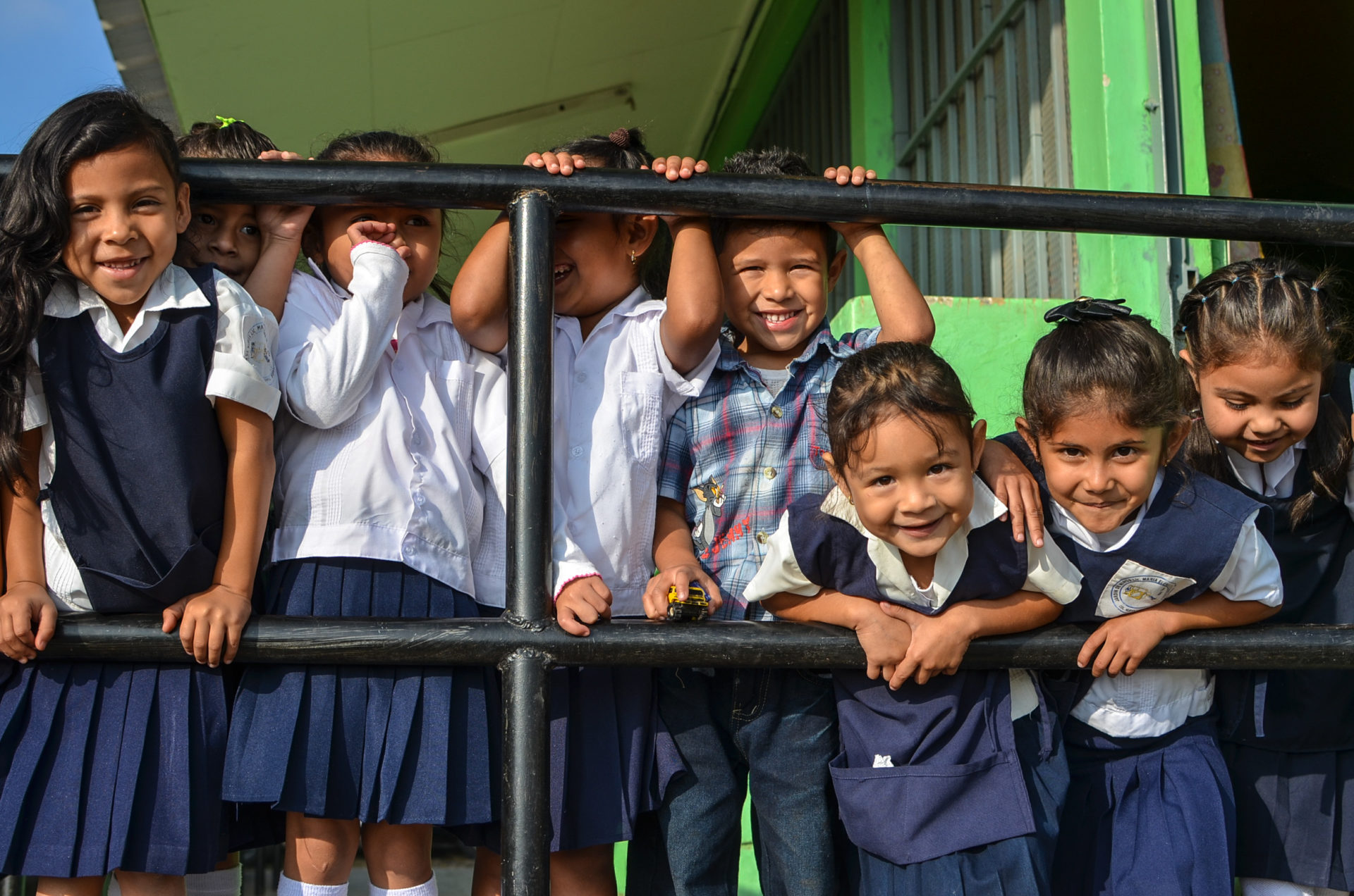 school children stand at a railing smiling